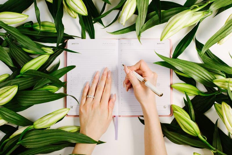 Фемининовые руки, пишущие в тетради, окруженные зелеными свежими цветами на белом фоне Красивая рабочая область стоковые фотографии rf