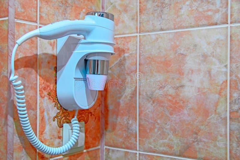 Фен для волос установленный стеной в гостиничном номере Плитка ванной комнаты скопируйте космос стоковое фото