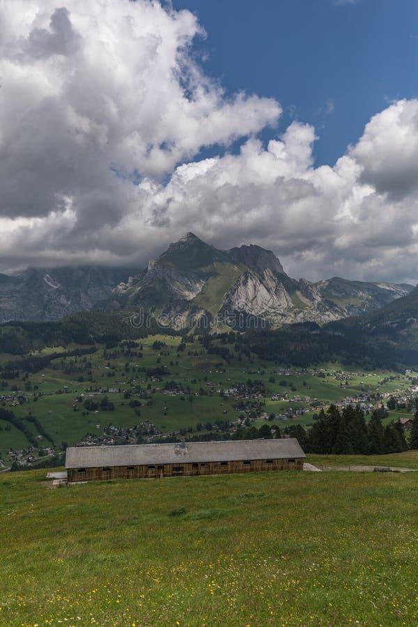 Ферма между красивыми швейцарскими горными вершинами около toggenburg стоковая фотография rf