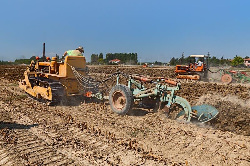 Фермер вспахивая поле с старым трактором crawler Фиат стоковые фотографии rf