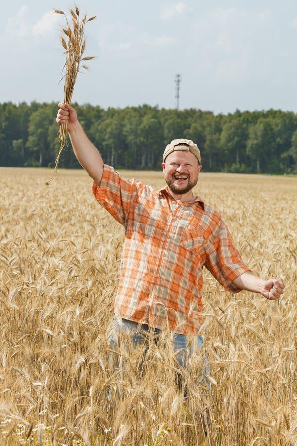 Фермер в крышке стоя на поле стоковые изображения