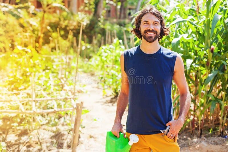 Фермер держа моча чонсервную банку в саде стоковое изображение