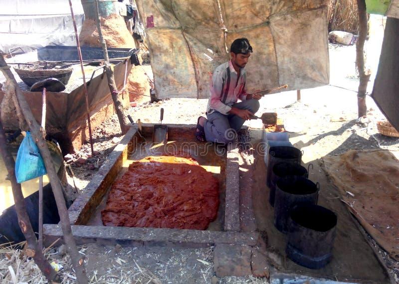 Фермер делая желтый сахарный песок (jaggery) в сельской Индии стоковое фото rf