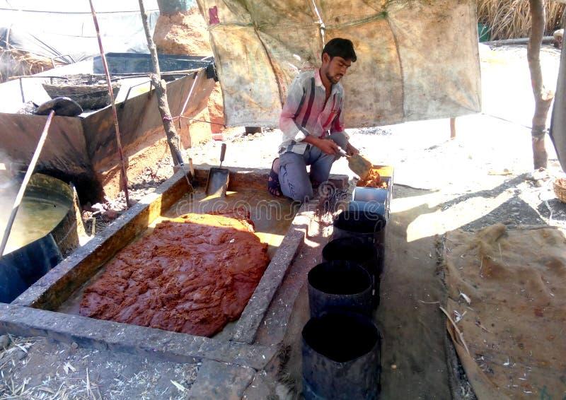 Фермер делая желтый сахарный песок (jaggery) в сельской Индии стоковое изображение rf