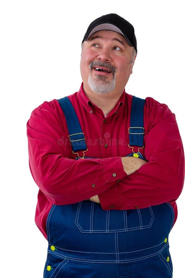 Фермер или работник в dungarees смотря вверх стоковая фотография rf