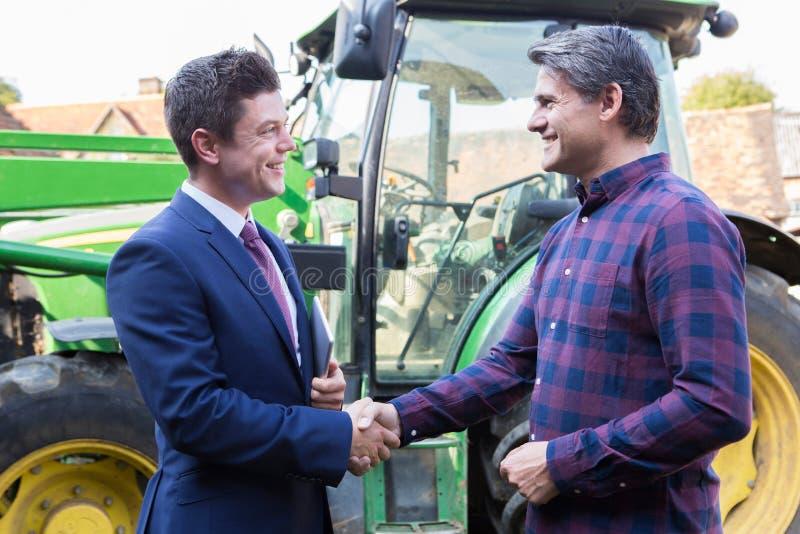 Фермер и бизнесмен тряся руки с трактором в предпосылке стоковое изображение