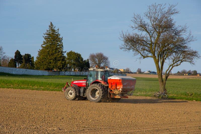 Фермер на удобрении трактора Ferguson massey распространяя стоковое фото