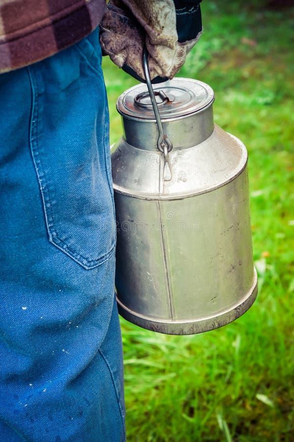 Фермер нося винтажную чонсервную банку молока молокозавода стоковые изображения rf
