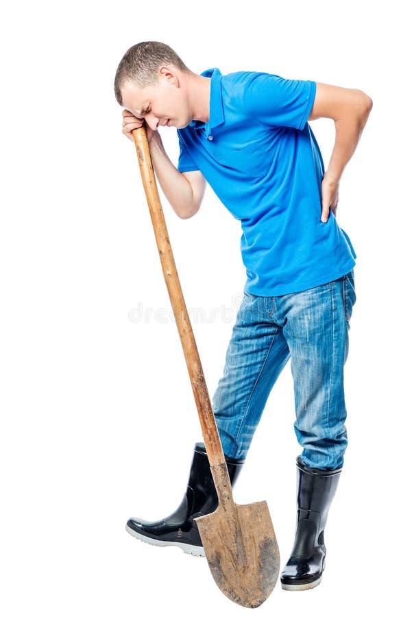 Фермер при лопаткоулавливатель держа его рука больное назад на белизне стоковая фотография