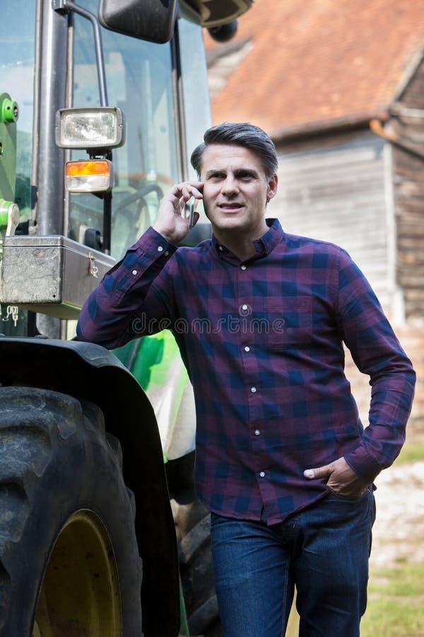 Фермер рядом с трактором говоря на мобильном телефоне стоковые изображения rf