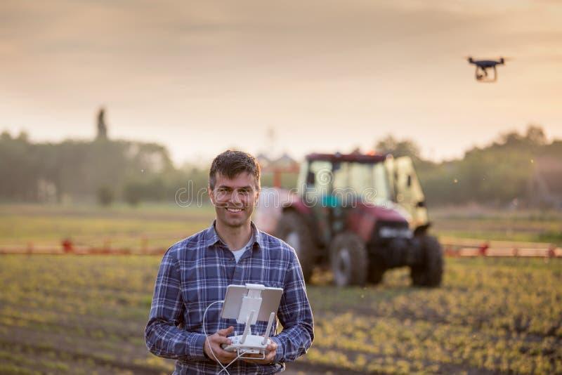 Фермер управляя трутнем над полем стоковые фотографии rf