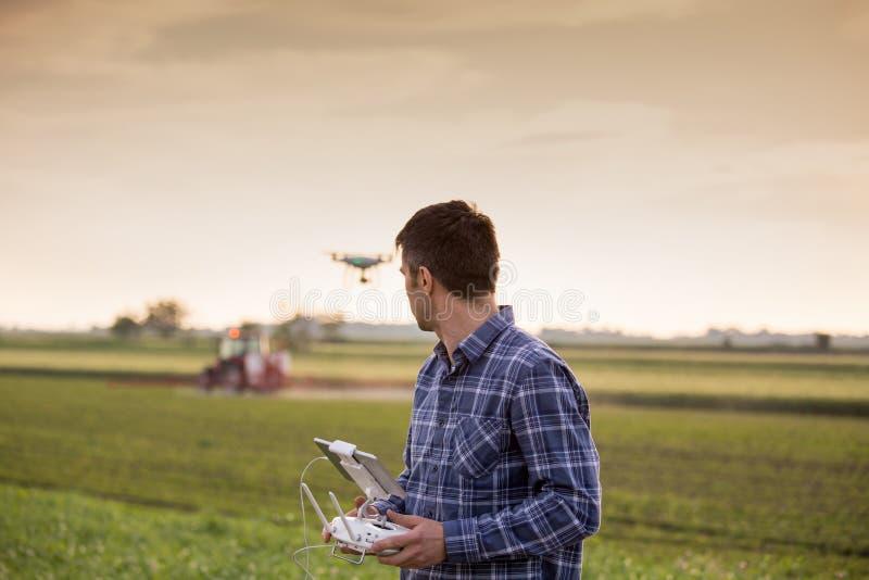 Фермер управляя трутнем над полем стоковые фото