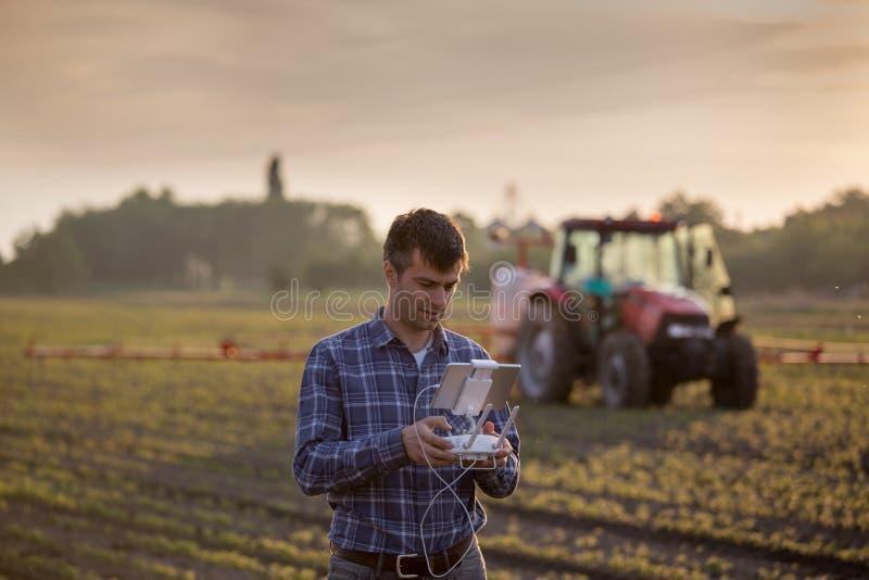 Фермер управляя трутнем над полем стоковое фото