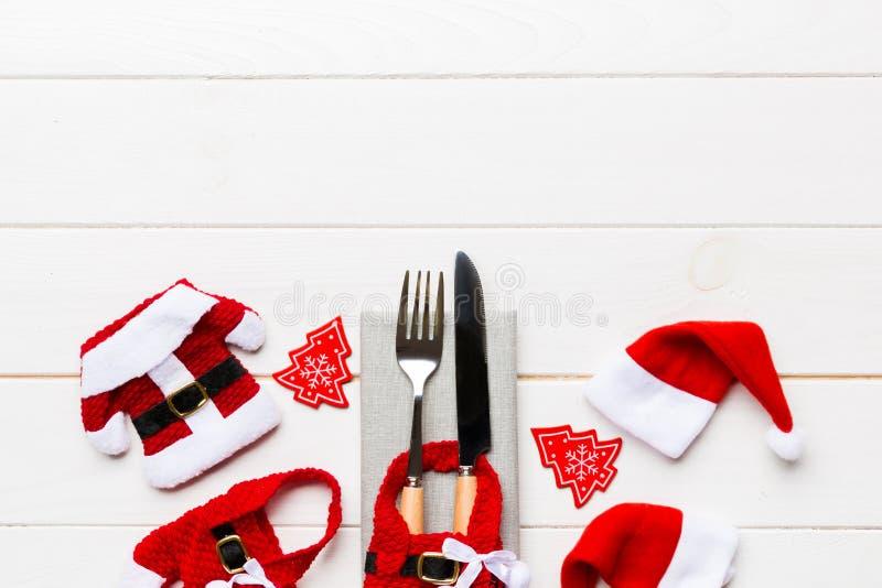 Фестивальный набор вилки и ножа на деревянном фоне Вид на новогодние декорации, санту и шляпу Рождественская концепция стоковая фотография rf