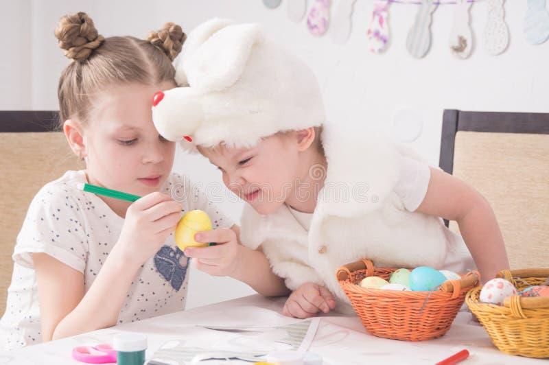 Фестиваль пасхи: пасхальные яйца краски детей на таблице Мальчик в костюме кролика смотрит хитро на работе более старого siste стоковое фото rf