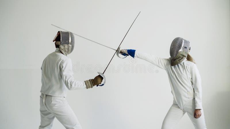 Фехтовальщик молодой женщины имея ограждать тренировку с тренером в белой студии внутри помещения стоковое фото