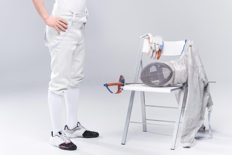 Фехтовальщик молодого человека профессиональный стоя близко стул с ограждать оборудование стоковое фото rf