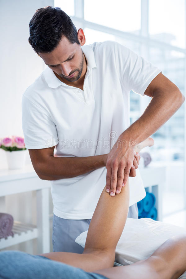 Физиотерапевт давая массаж ноги к женщине стоковые фото