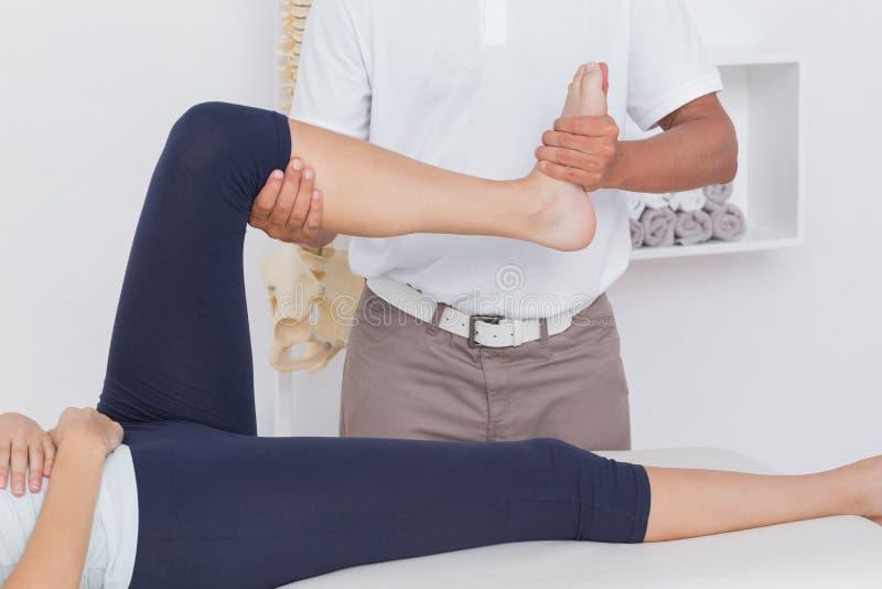 Физиотерапевт делая массаж ноги к его пациенту стоковое фото