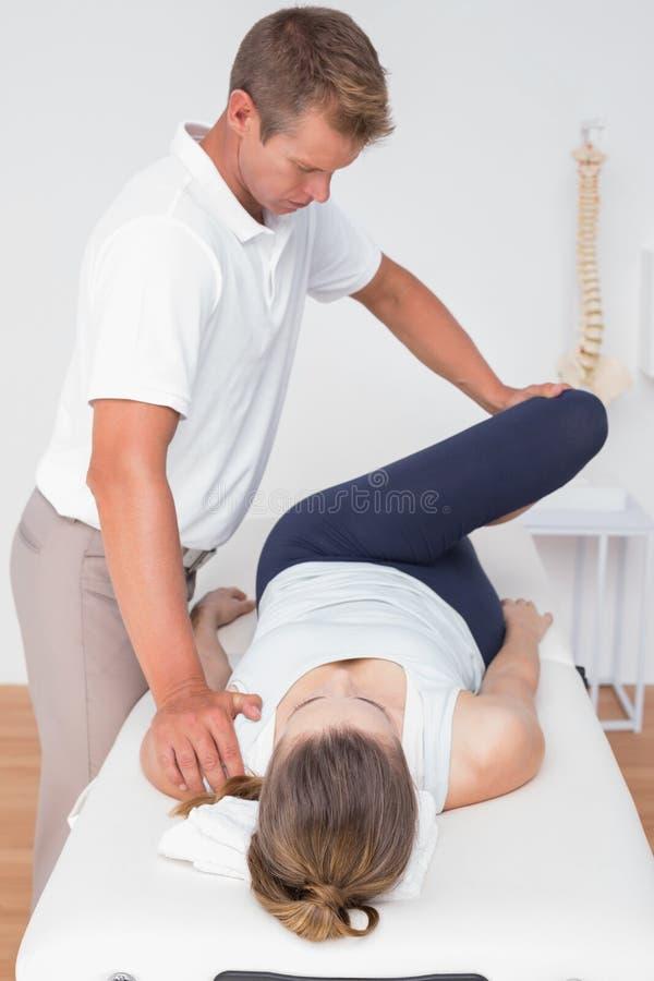 Физиотерапевт делая массаж ноги к его пациенту стоковые изображения rf