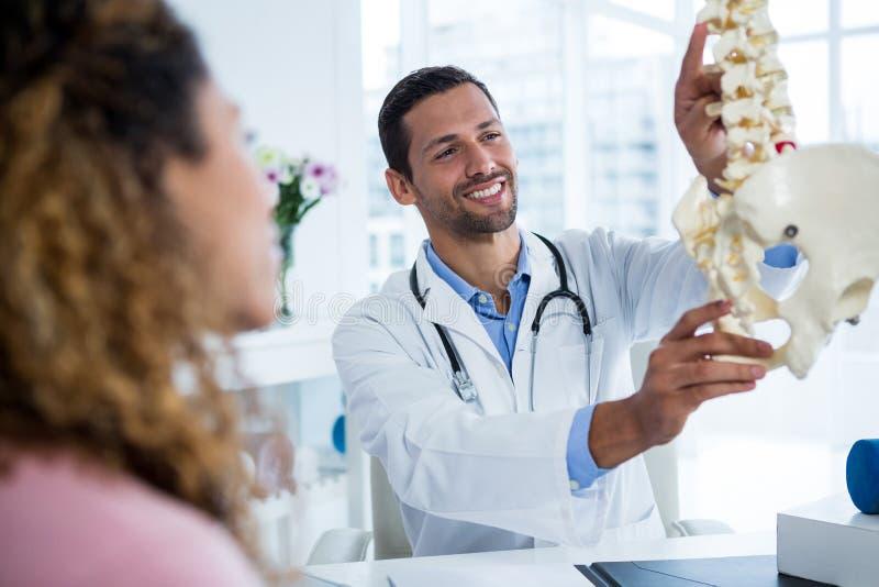 Физиотерапевт объясняя модель позвоночника к пациенту стоковые фотографии rf