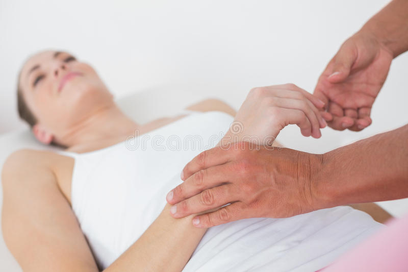 Физиотерапевт рассматривая ее терпеливую руку стоковое фото rf