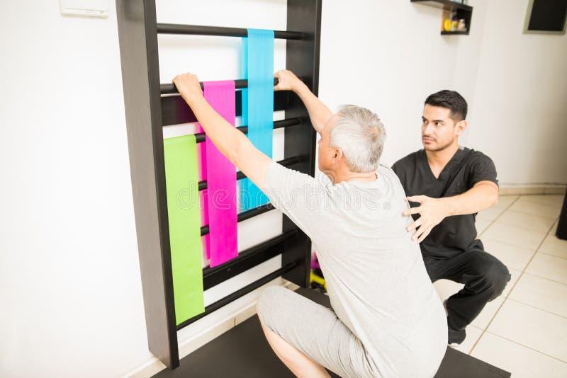 Физиотерапевт смотря бары стены пока помогающ пациенту Doi стоковое изображение rf