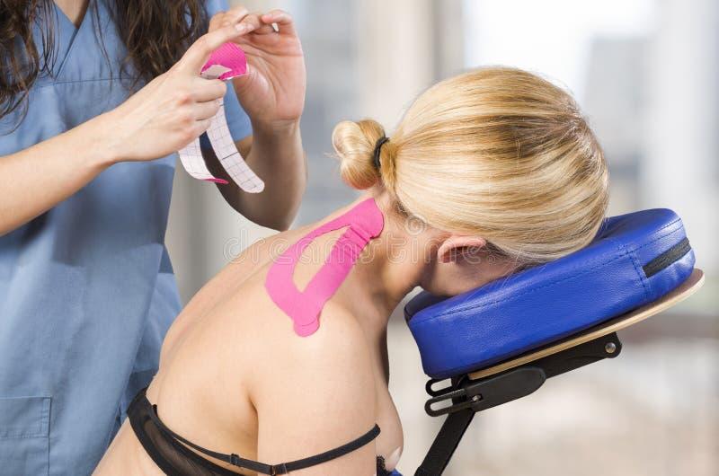 Физиотерапевт, хиропрактор кладя на розовую ленту kinesio на wo стоковые фото