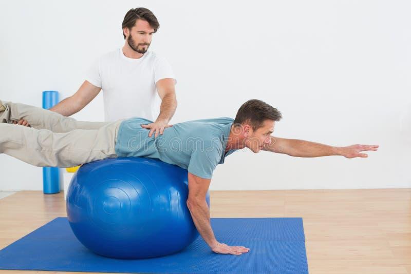 Физический терапевт помогая молодому человеку с шариком йоги стоковая фотография rf