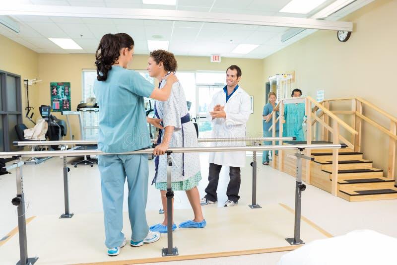 Физический терапевт помогая пациенту в идти стоковая фотография rf
