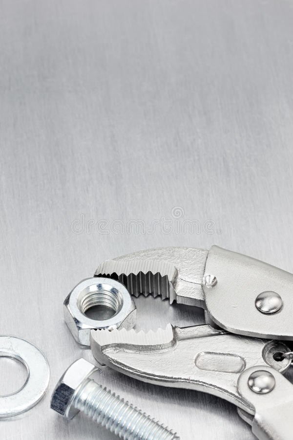 Фиксировать-челюсть и болты для работы руки и ремонта дома стоковая фотография
