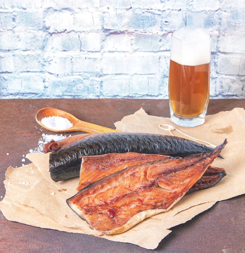 Филе копченой скумбрии на бумаге ремесла со стеклом пива на деревенской ржавой таблице металла стоковое изображение rf