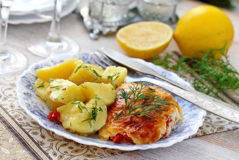 Филе рыб испеченное с томатом, зелеными цветами и сыром служило с кипеть картошками стоковые фотографии rf