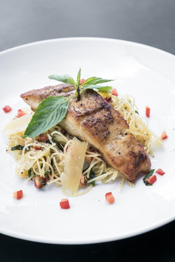 Филе свежих рыб на смешанном прошлом спагетти овоща и пармезана стоковые изображения