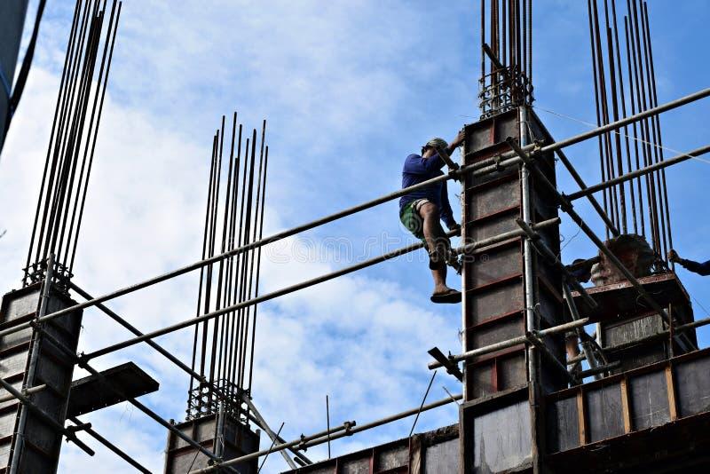 Филиппинский стал-человек конструкции взбираясь вниз используя леса пускает по трубам на многоэтажном здании стоковое изображение rf