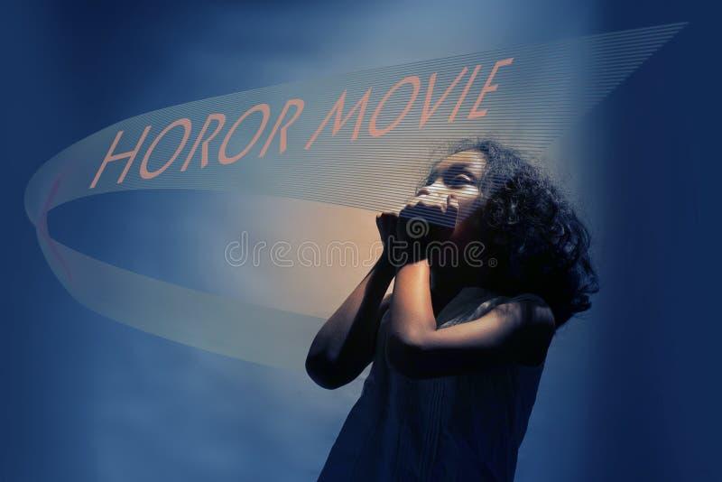 Фильм ужасов Ужаснутая маленькая девочка смотря фильм на кино Девушка с сотрясенным выражением смотря фильм в театре стоковые изображения rf