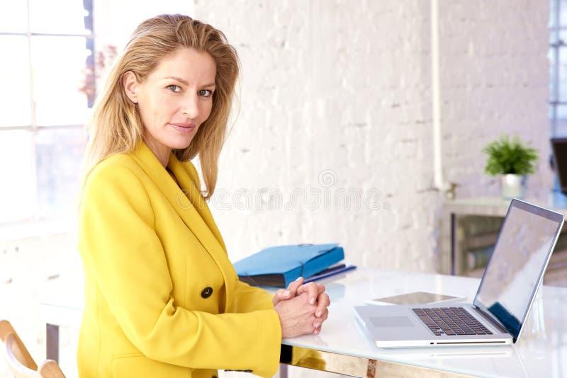 Финансовая бизнес-женщина, работающая над своим ноутбуком в офисе стоковое фото