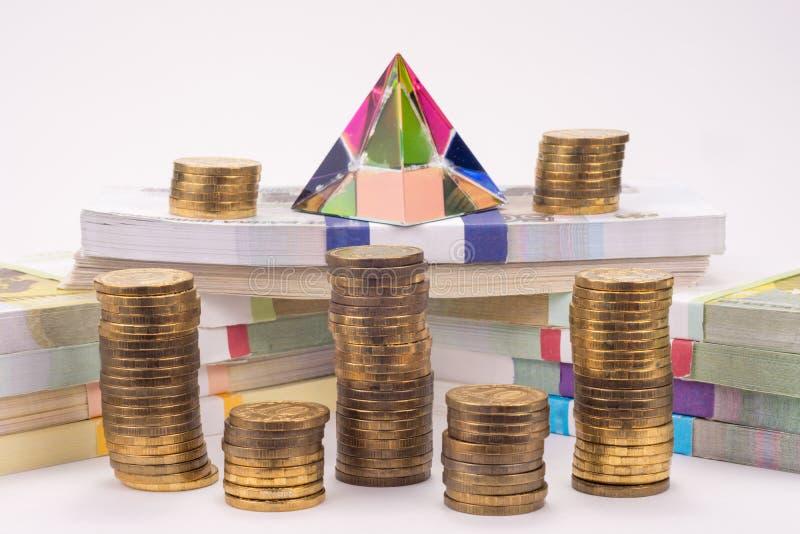 Финансовая пирамида, валюшки денег и стога монеток стоковое фото rf