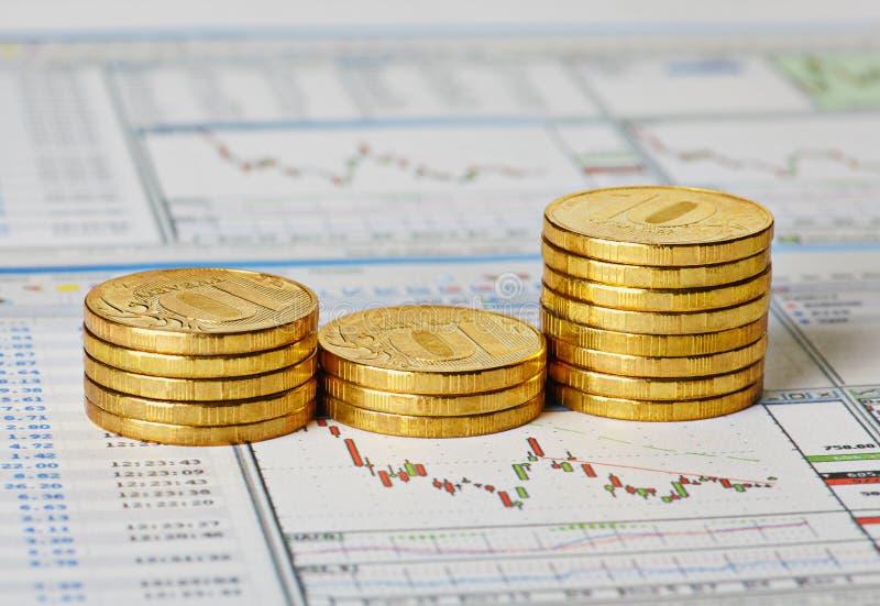 Финансовохозяйственный выселок с диаграммами и золотистыми монетками. стоковое фото rf