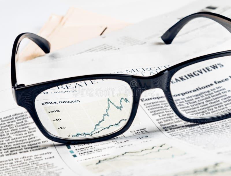 Финансовые диаграмма и диаграмма фондовых индексов видят до конца объектив стекел на финансовой газете стоковые изображения