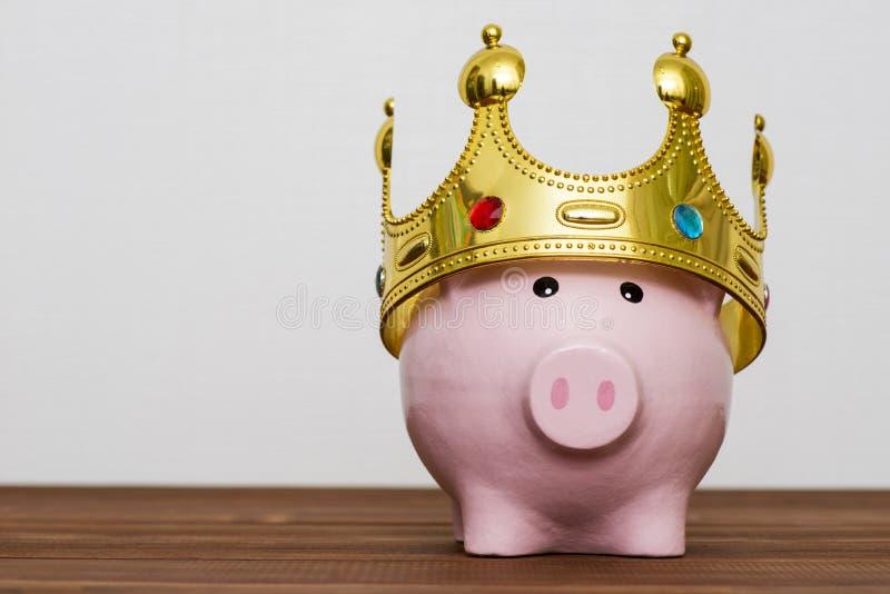 Финансовые победитель или король концепции сбережений денег, усмехаясь счастливая розовая копилка нося золотую крону на деревянно стоковое изображение
