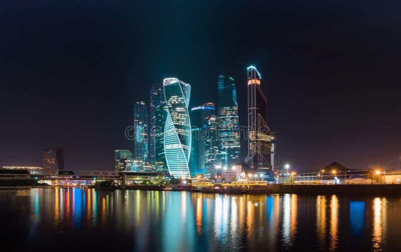 Финансовый район города в красочной ноче освещает Полуночные света большого города Москвы отражены в реке стоковое изображение rf