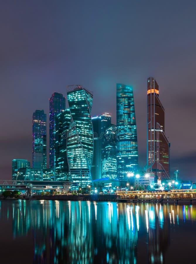 Финансовый район Москвы в красочной ноче освещает Крыши зданий в тумане стоковое фото rf