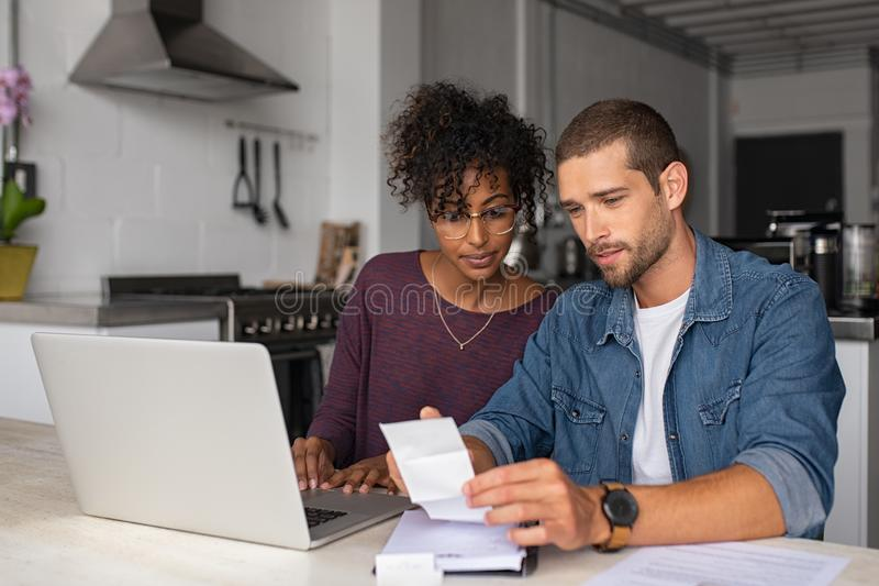 Финансы молодых многонациональных пар рассматривая домашние стоковая фотография rf