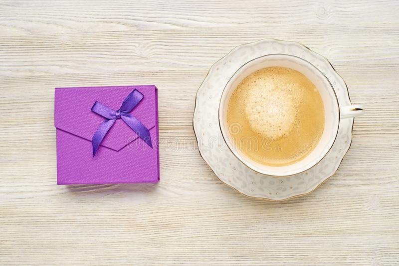 Фиолетовая подарочная коробка с чашкой смычка и капучино на светлом деревянном ба стоковое фото