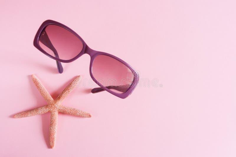 Фиолетовые солнечные очки и морские звёзды на розовой предпосылке красивейшие детеныши женщины каникулы бассеина принципиальной с стоковая фотография