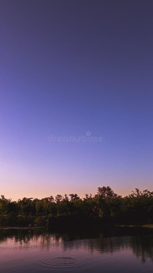 Фиолетовый заход солнца в озере стоковое фото rf