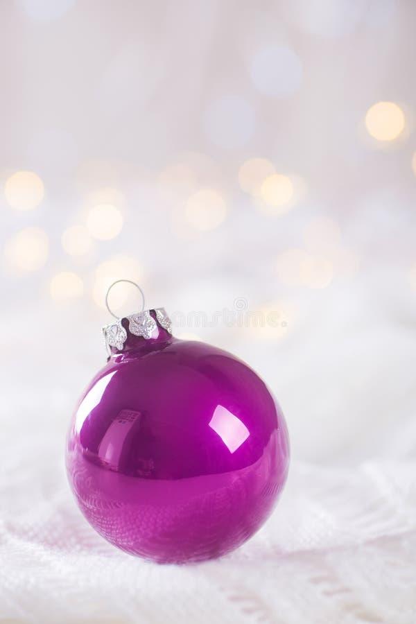 Фиолетовый шарик рождества на белом шнурке на светлой и теплой задней части bokeh стоковое изображение rf