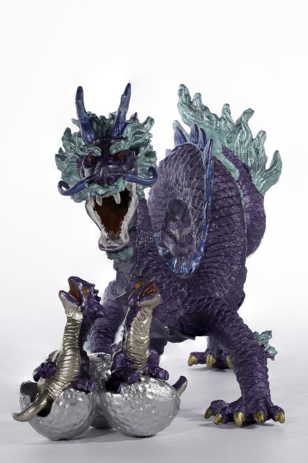 Фиолетовый Figurine дракона защищая свои цыпленоки насиживать II стоковое фото rf