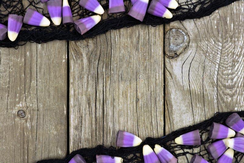 Фиолетовая мозоль конфеты хеллоуина и черная рамка ткани против древесины стоковые изображения rf
